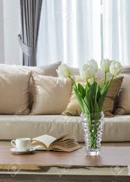 living room sofa with flower coffee and book on table stock photo