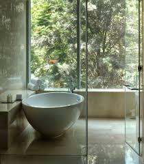 round glossy stone bathtub on sleeky cream marble flooring plus