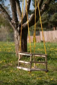 swing in a garden full of flowers stock photo colourbox