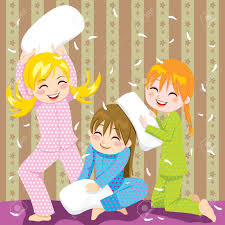 three young girls having fun doing pillow fight in a pajama party
