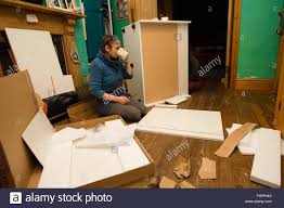 a middle aged woman preparing to assemble a set of flat pack ikea