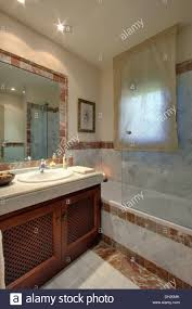 glass shower screen on bath in modern spanish bathroom with voile