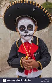 young boy with face painted and dressed in traditional costume for