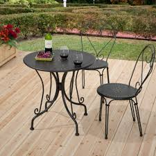 round black wrought iron table with curving legs also black iron