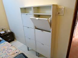 tall white wooden shoe cabinets with six shoes racks and shelf
