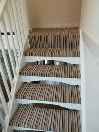 indoor open staircase with striped runners installing a carpet