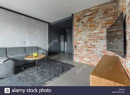 Gray Living Room With Sofa Table Curved Tv And Industrial Brick