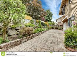 backyard area with stone tile floor and beautiful flower bed stock