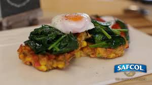 poached tuna corn and tuna fritter stack with poached eggs and spinach