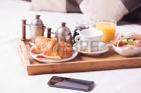 breakfast in bed tray with coffee croissants and fruits stock