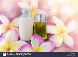 mini set of bubble bath and shower gel liquid with pink flowers mini set of bubble bath and shower gel liquid with pink flowers plumeria or frangipani on timber or log wooden background shampo