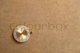 old rusty watch dial on textured wall background stock photo