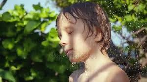 pretty verry young boys washing hairs boy playing with water in the garden boy has a shower washing