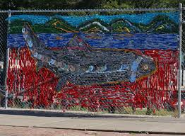 block renaissance newport artists create murals on fencing around the fish sculpture has been recreated in fabric and old dvds on the main street fence