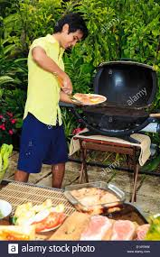 Outdoor Barbecue Hawaii Young Man Preparing Outdoor Barbecue Feast In Hawaii