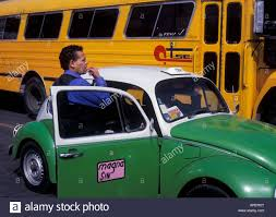 yellow volkswagen beetle royalty free taxi driver and vw beetle taxi with bus in mexico city stock photo