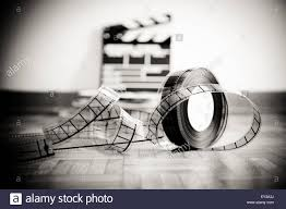 size positioning custom wallpaper caption 35 mm cinema film reel and out of focus movie clapper board in background on wooden floor in vintage black and white wall mural related terms 35