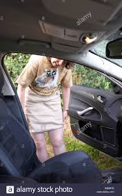 woman pulling down skirt after relieving herself by parked car