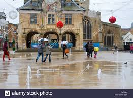 peterborough city centre people walk across fountain and
