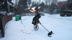 Shoveling Snow Meme - man shoveling snow on a unicycle dressed as darth vader while