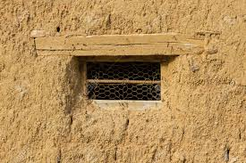 small window in old adobe house with wire mesh and wooden lintel