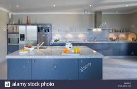large modern blue kitchen with island unit and pale grey granite
