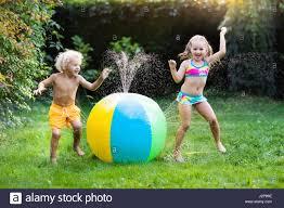 child playing with toy ball garden sprinkler preschooler kid run