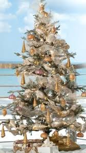 snow dusted tree with golden blown glass shell ornaments
