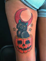 halloween cat in pumpkin with half moon tattoo on thigh
