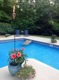 Tiki Backyard Designs by Tiki Torches In The Flowers Around The Pool Inground Pools