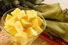 fresh pineapple chunks served in a contemporary glass bowl stock