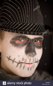 young boy in skull makeup for halloween wearing a dark striped hat