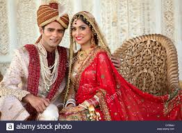 indian bride and groom in traditional wedding dress sitting on a