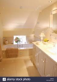 cream floor tiles in modern attic bathroom with downlighting and