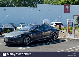 tesla charging electric car charging station with a tesla sedan plugged in tesla