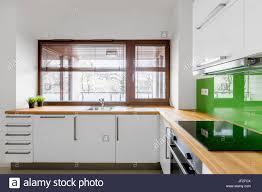 white kitchen with modern cupboards green backsplash and window