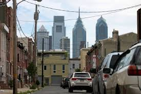 the philadelphia skyline towering over the row homes of south