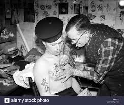 tattooist applying sailor to the chest of a sailor on the