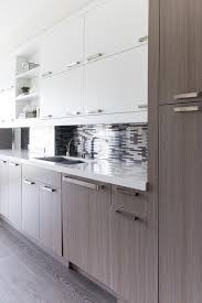oak veneer kitchen cabinets with silver and gray mosaic tiles
