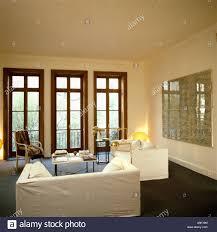 white sofas in modern white livingroom with tall windows stock