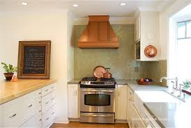 kitchen designed with white cabinets and copper hood over kitchen