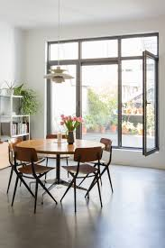 bright dining room with concrete floor vintage chairs and table