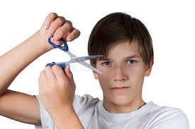 cutting boy hair with scissors young boy cutting his hair with scissors stock photo image of