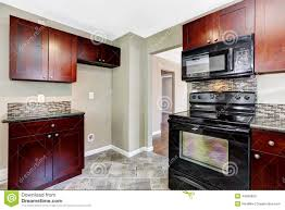 Black Kitchen Cabinets With Black Appliances by Kitchen With Bright Burgundy Cabinets And Black Appliances Stock