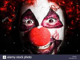 close horror portrait on the face of a scary and evil clown