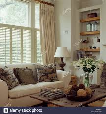 cream curtains and plantation shutters on window above cream sofa
