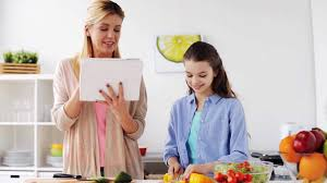 man using electronic tablet pc in kitchen man searching food