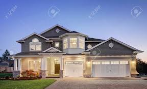 beautiful luxury home exterior at night with three car garage beautiful luxury home exterior at night with three car garage driveway grass yard