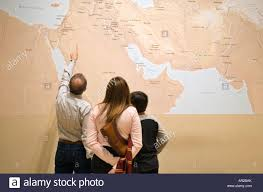 A Map Of The Middle East by Arabic Family Looking At A Map Of The Middle East In The