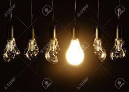 single light bulb with cord a single light bulb glowing among broken bulbs on a black background